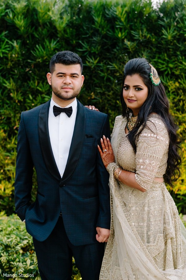 Indian couple in their reception outfits.