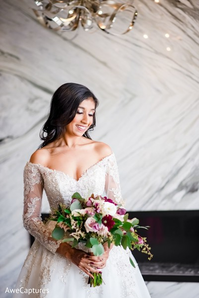 Incredible Indian bride on her white wedding dress and bouquet.