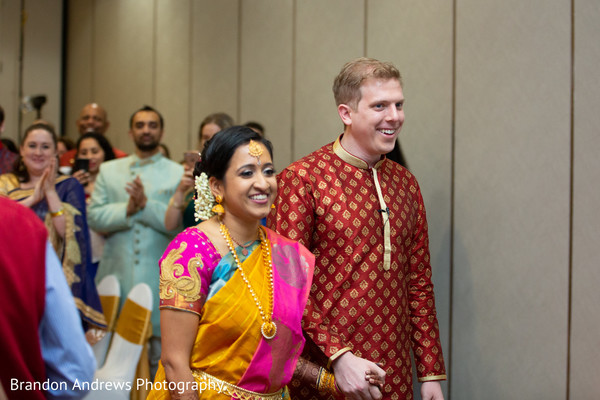 Joyful Indian couple walking out of ceremony.