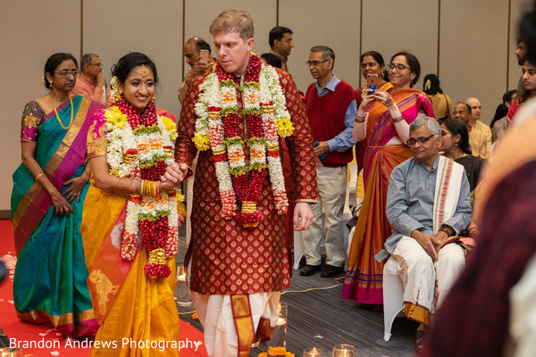 Indian couple walking out of Indian wedding ceremony.