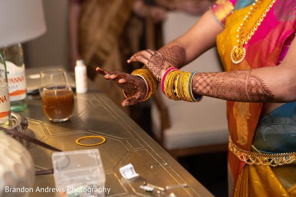 Closeup capture of maharani putting her bangles on.