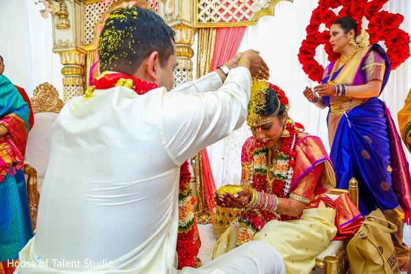 Indian groom pouring rice to bride ritual.