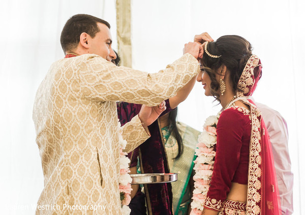 Indian groom putting the red mark on maharanis forehead.