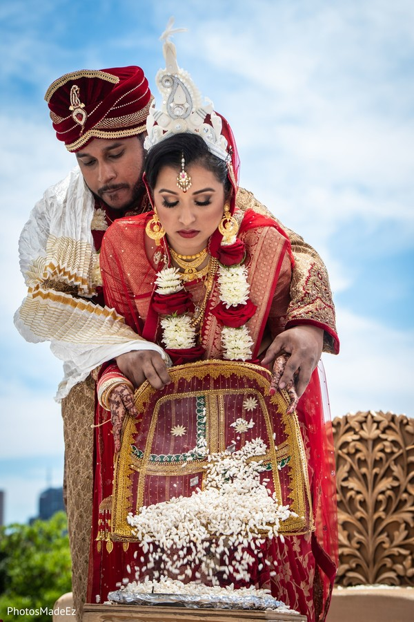 Indian couple pouring rice at wedding ceremony.