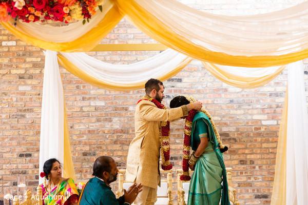 Indian groom putting flower garland to bride