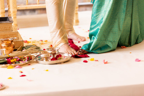Indian bride and groom stepping on the nuts ritual.