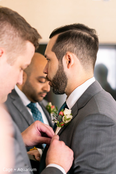 Indian groom being assisted by one of his groomsmen.