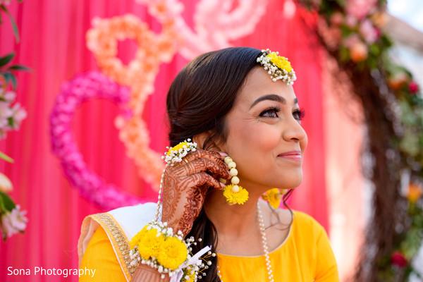 Indian bride putting her flowers earrings.