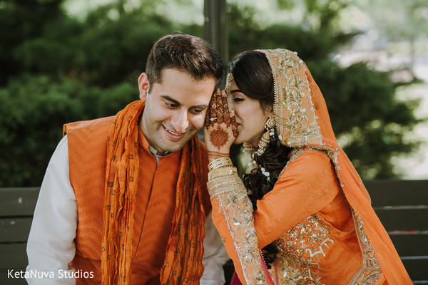Lovely Indian bride telling her groom a secret.