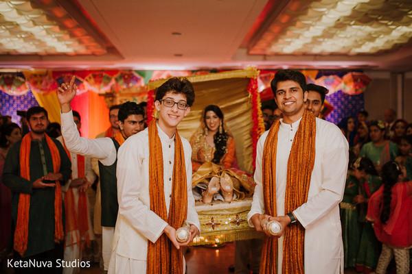 Cheerful groomsmen carriyng Indian bride on her Doli.