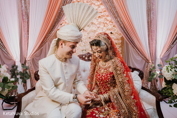 Indian groom putting ring on his gorgeous bride.
