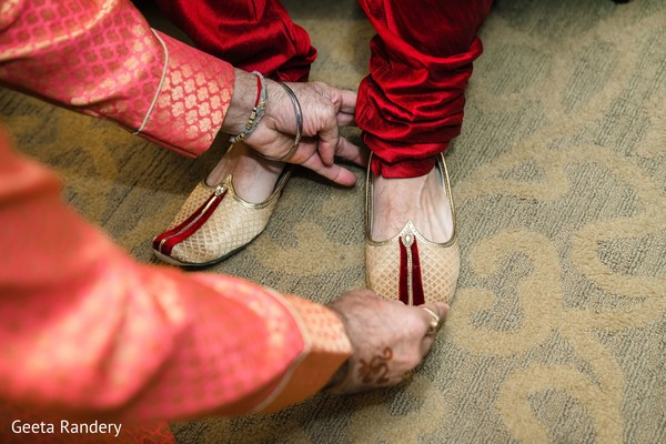 Indian groom being assisted to put his elegant shoes on.