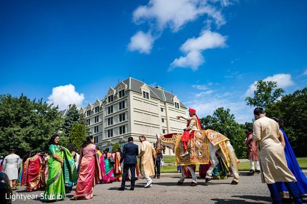 Elegant Indian groom riding baraat white horse
