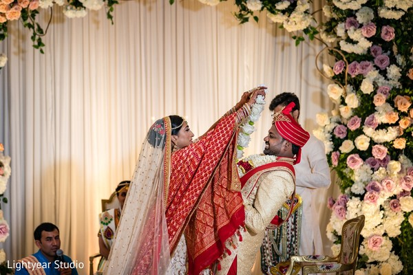 Indian bride putting flower garland to groom