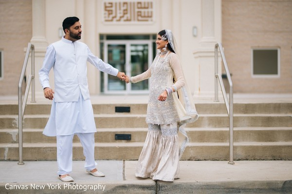 Gorgeous Indian bride  and groom in white traditional outfits.