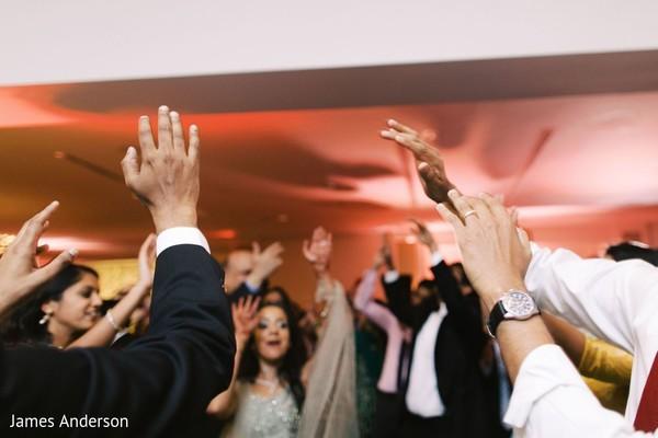 Upbeat Indian wedding  guests dancers.