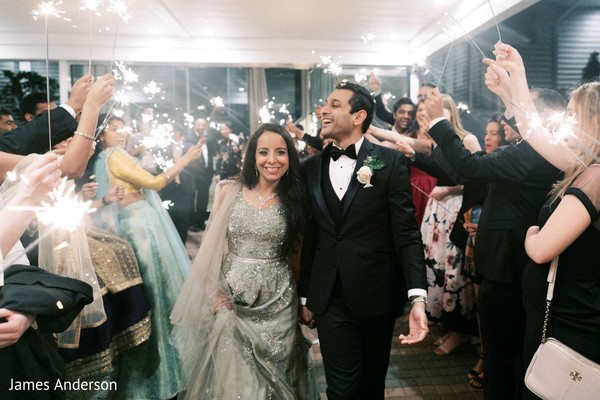 Dazzling Indian bride and groom walking down the aisle.