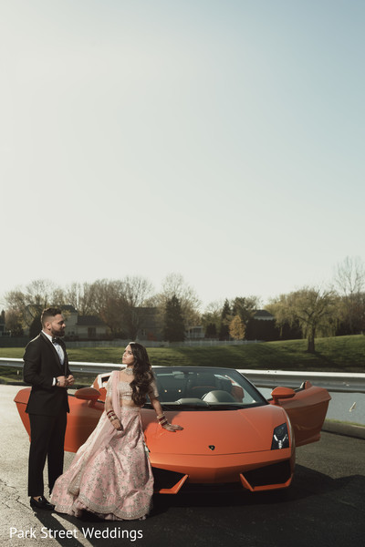 Indian bride and groom posing with the car.