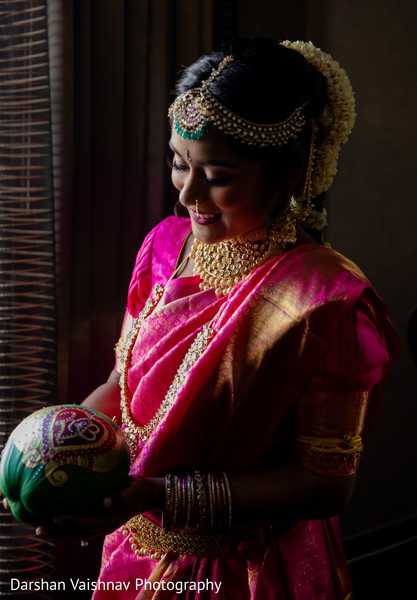 Enchanting Indian bride holding her ritual coconut.