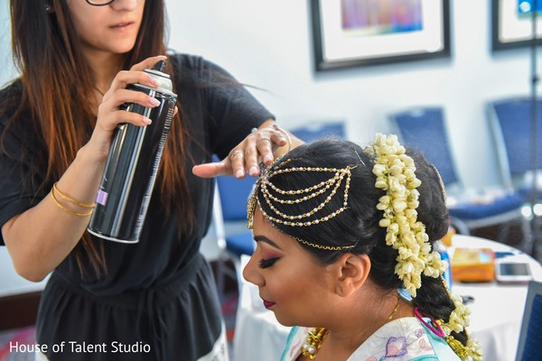 Indian bride being assisted by makeup artist.