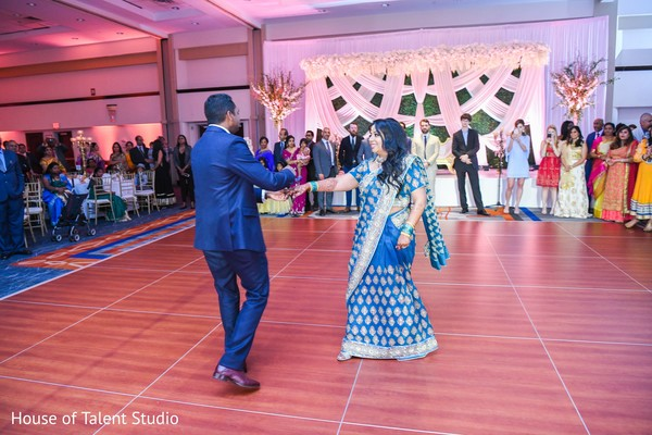 Indian bride and groom holding hands.