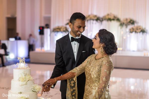 Lovely Indian couple cutting the wedding cake.
