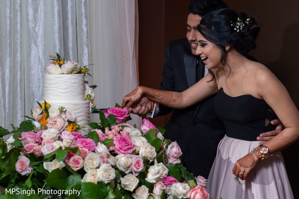 Indian bride and groom cutting the cake.