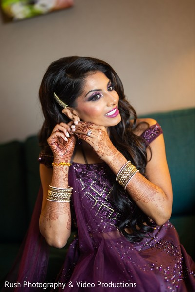 Enchanting Indian bride putting her earrings on.