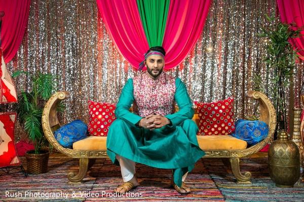Indian groom posing at sangeet stage.
