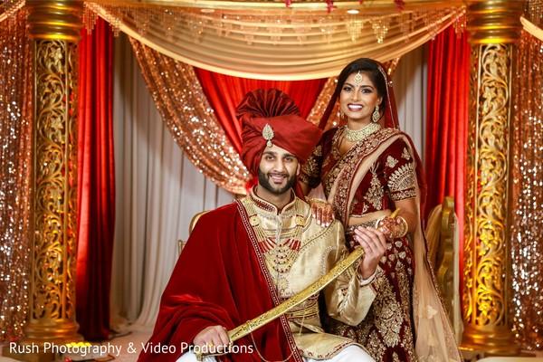 Glamorous indian couple posing at mandap.