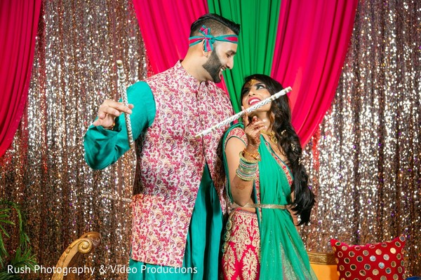 Joyful indian couple with dandiya raas sticks.