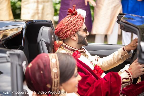 Joyful Indian couple leaving ceremony.