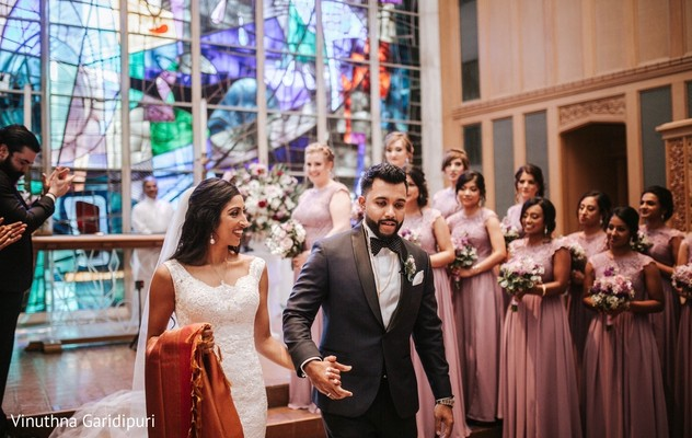Elegant Indian couple walking married off the altar.