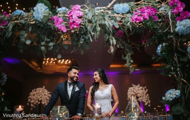 Joyful Indian couple surrounded by flowers.
