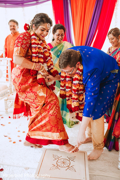 Indian groom putting toe ring to bride at ceremony.