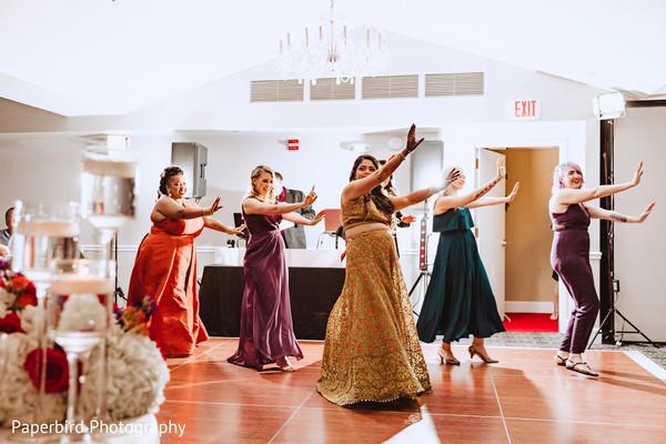 Adorable indian bride dancing with bridesmaids.