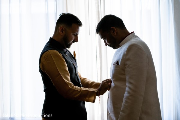 Indian groom assisted by his best man.