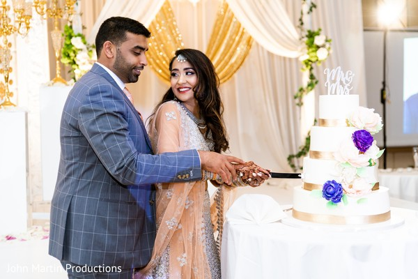 Lovely Indian couple cutting the delicious wedding cake.