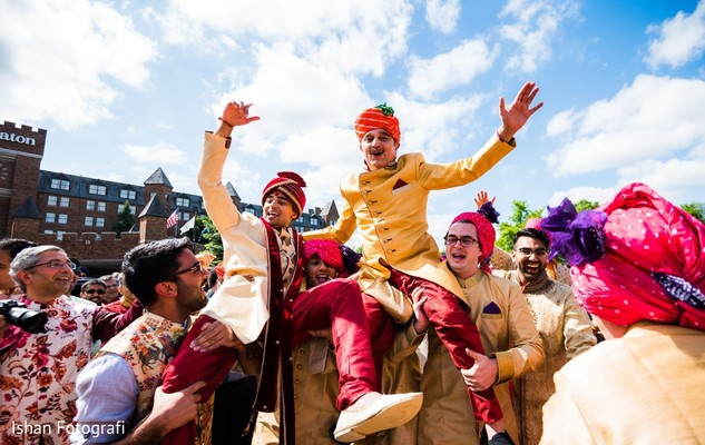 Indian groom being lifted up during baraat