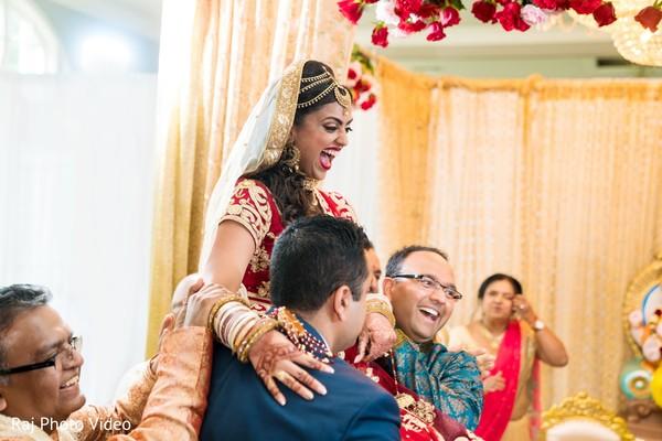 Joyful Maharani being carried by groomsmen.