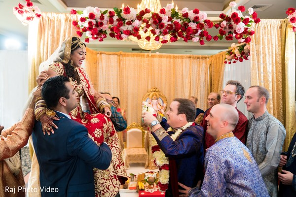 Indian groom about to put garland on his bride.