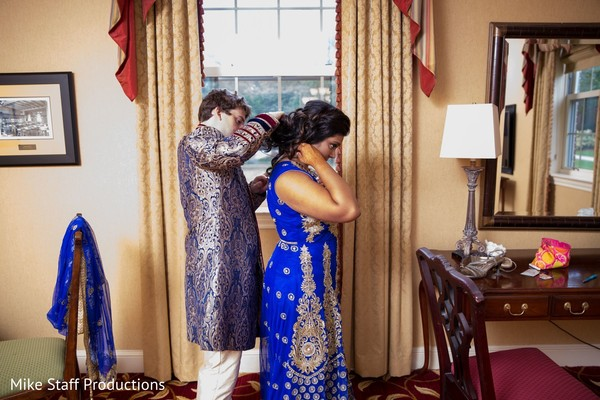 Indian groom helping bride to get ready.
