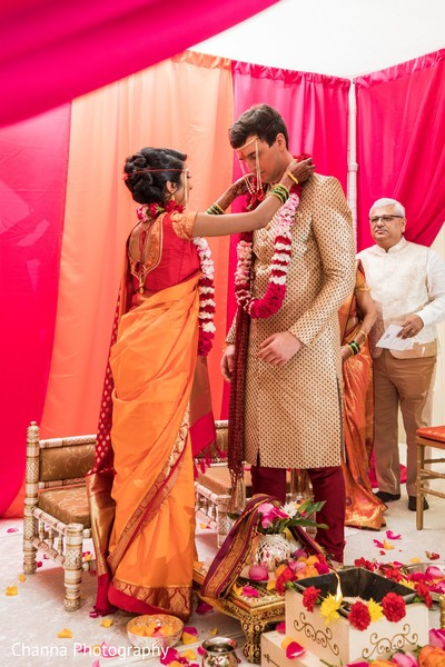 Sweet Indian bride putting garland to groom.