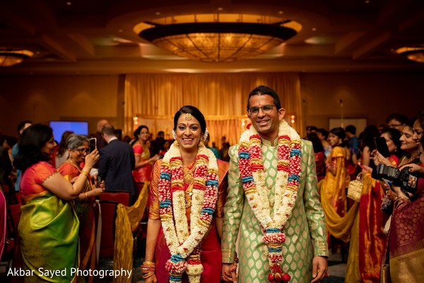 Indian bride and groom walking out from their ceremony