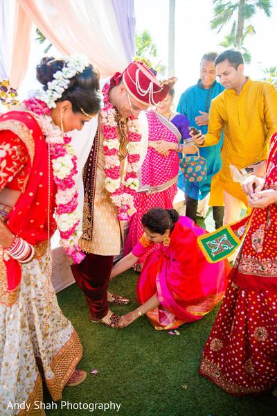 Indian bridesmaid putting grooms mojaris.