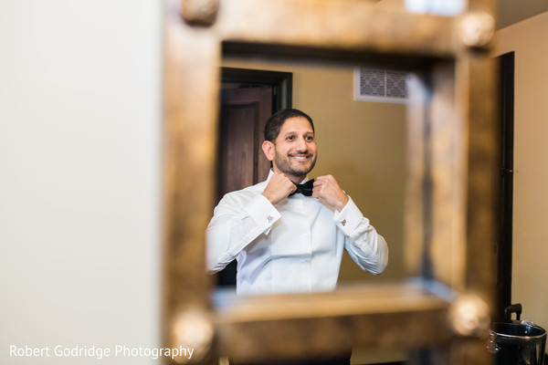 Charming indian groom looking in the mirror