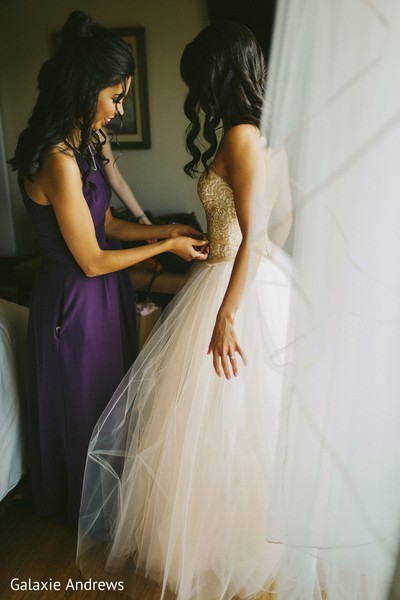 Indian bridesmaid helping Indian bride getting ready.