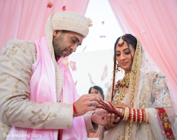 Indian groom putting ring to bride ritual.