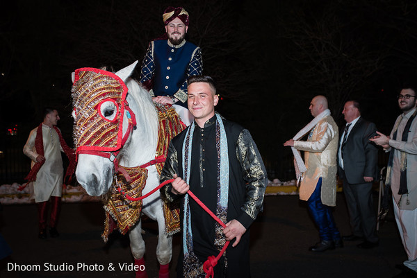 Happy Indian groom arriving on his majestic horse.