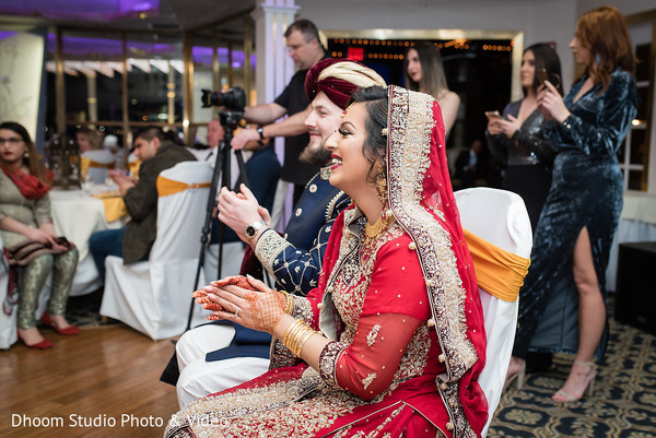 Joyful Indian couple clapping together.